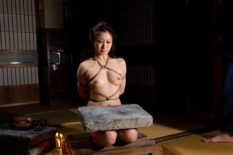 全裸で正座する足の上に石が…